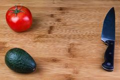 A Tomato and an Avocado on a cutting board with a Chef`s knife royalty free stock photography