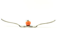 Tomato in balance on two forks Stock Photography