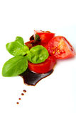 Tomato and balsamic vinegar. Fresh tomato and basil over olive oil and balsamic vinegar royalty free stock image