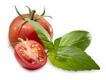 Tomato basil. Whole tomato with an half tomato in front and three leafs of basil against white Royalty Free Stock Image