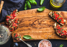Tomato and basil bruschetta with glass of white wine on olive wooden board over black background Stock Photo