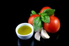 Tomato, basil, garlic, olive oil 1. Basil, tomato,garlic and olive oil, fresh ingredients, isolated on black background Stock Images