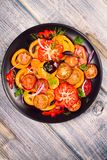 Tomato, basil, parsley, dill and onion salad. View from above, top studio shot, vertical Royalty Free Stock Photos