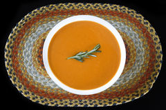 Tomato Basil Soup. A creamy tomato basil bisque sits on a multicolored jute placemat. A sprig of rosemary garnishes the dish stock images
