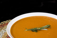 Tomato Basil Soup 2. A creamy tomato basil bisque sits on a multicolored jute placemat. A sprig of rosemary garnishes the dish royalty free stock images