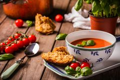 Tomato basil soup. Tomato and basil soup shot on wood boards angled view with vine tomatoes loose basil spoon copper pot basil plant bread landscape Stock Photo