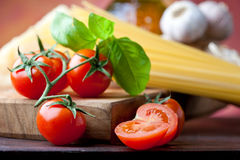 Tomato, basil and spaghetti. Raw pasta with tomato, basill, garlic, Parmesan cheese and olive oil close up Stock Photo