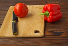Tomato and bell pepper on a cutting table. stock image