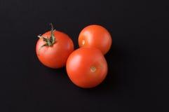 Tomato on black. Three tomato on black background Royalty Free Stock Photography