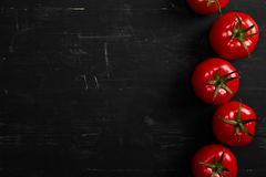 Tomato on a black background with realistic reflection and water drops. Fresh tomatoes. In a large amount Stock Photo