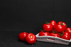 Tomato on a black background with realistic reflection and water drops. Fresh tomatoes. In a large amount Stock Photography