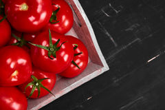 Tomato on a black background with realistic reflection and water drops. Fresh tomatoes. In a large amount Stock Image
