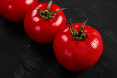 Tomato on a black background with realistic reflection and water drops. Fresh tomatoes. In a large amount Royalty Free Stock Image