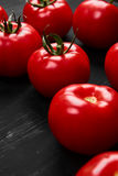 Tomato on a black background with realistic reflection and water drops. Fresh tomatoes. In a large amount Royalty Free Stock Photography