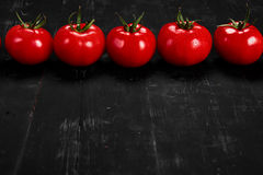 Tomato on a black background with realistic reflection and water drops. Fresh tomatoes. In a large amount Stock Images