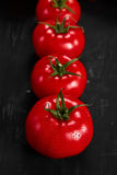 Tomato on a black background with realistic reflection and water drops. Fresh tomatoes. In a large amount Royalty Free Stock Photo