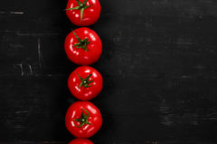 Tomato on a black background with realistic reflection and water drops. Fresh tomatoes Stock Images