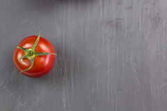 Tomato. On the black service stone Royalty Free Stock Photo