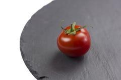 Tomato on black service stone. Tomato on the black service stone on isolated white background Royalty Free Stock Photos