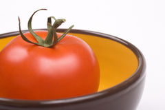 Tomato in a bowl. One tomato in a yellow with brown jar Royalty Free Stock Photography