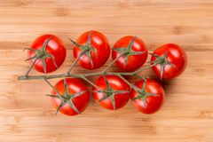 Tomato branch on vintage wood table Stock Images