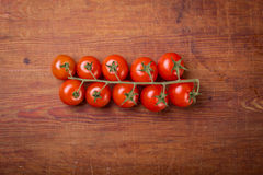 Tomato branch on vintage wood table Royalty Free Stock Image