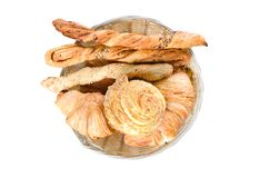 Tomato bread sticks, croissants and a bun in a wooden plate on white background royalty free stock photos