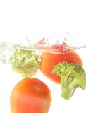 Tomato and broccoli vegetables splash Royalty Free Stock Photos