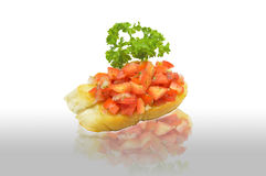 Tomato bruschetta decorated with parsley leaf on the floor reflection on white background Stock Photos