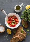 Tomato bruschetta. Tomato basil salad, whole grain baguette on dark background, top view. Delicious vegetarian appetizer Stock Photos