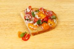 Bruschetta on a chopping board. Tomato bruschetta on a wooden chopping board Royalty Free Stock Photo