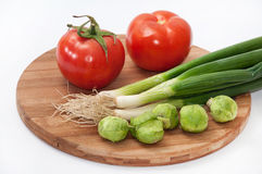 Tomato, brussels sprouts and green onions on a wooden board Royalty Free Stock Photos