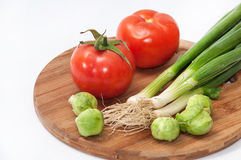 Tomato, brussels sprouts and green onions on a wooden board Stock Photos