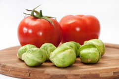 Tomato and brussels sprouts on a wooden board Stock Photography