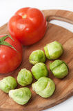Tomato and brussels sprouts on a wooden board Royalty Free Stock Image