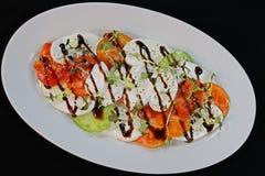 Tomato buffalo mozzarella salad in a white plate stock images