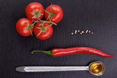 Tomato bunch, chili pepper, grains of white pepper,  spoon of olive oil  on dark stone Stock Image