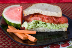 Tomato and Butter Lettuce Sandwich. On a black plate with carrot sticks and watermelon slices Royalty Free Stock Photos