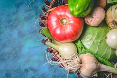 Tomato, cabbage, onion, potato, pepper, garlic, carrot and beetroot. Vegetables in a basket on a blue background. Copy space. Healthy food, agriculture stock photo