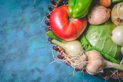 Tomato, cabbage, onion, potato, pepper, garlic, carrot and beetroot. Vegetables in a basket on a blue background. Copy space. Healthy food, agriculture stock photography