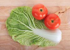 Tomato and cabbage on wooden chopping Royalty Free Stock Photography
