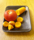 Tomato and carrot. Fresh tomato and carrot, photography in the foreground Royalty Free Stock Image