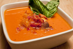 Tomato Carrot Soup. Garnished with croutons, bacon bits and basil Royalty Free Stock Image