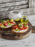 Tomato and cheese bruschetta on a rustic wooden cutting board. Stock Photo