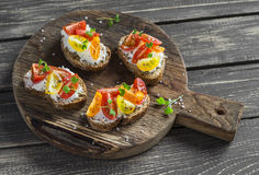 Tomato and cheese bruschetta on a rustic wooden cutting board. Healthy breakfast, snack Stock Photography