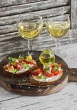 Tomato and cheese bruschetta and two glasses of white wine on a rustic wooden cutting board. Stock Photo