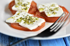 Tomato and cheese, dressed with olive oil and oregano. Closeup of a white ceramic plate with some slices of tomato topped with fresh cheese and dressed with royalty free stock photo