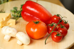 Tomato, cheese, onion on wooden plate Stock Photos