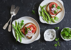 Tomato and cheese sandwiches and green beans is a healthy vegetarian breakfast or snack on a dark table, top view. Stock Photography