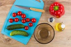 Tomato, cucumbers, knife on cutting board, pepper, salt, vegetable oil. Tomato cherries, cucumbers, kitchen knife on blue cutting board, sweet pepper, salt stock image